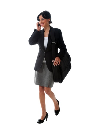 Happy businesswoman is walking and talking at the phone. photo