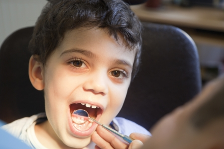 Dentist is checking and treating little boys teeth. photo