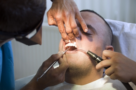 Dentist is checking and treating his patiences teeth. photo