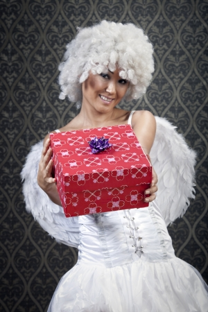 Happy girl in white angel costume with colorful gift box. photo