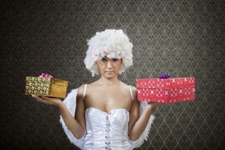 Happy girl in white angel costume with colorful gift boxes. photo