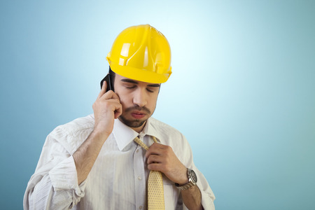 Young civil engineer is having trouble over the phone. photo