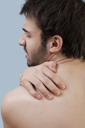 Young male is having a pain in his shoulder. photo