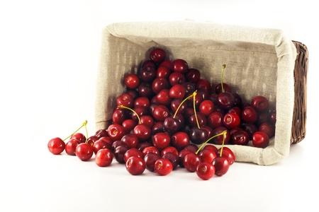 overturn: Un cesto di rovesciare con ciliegie versato su uno sfondo bianco