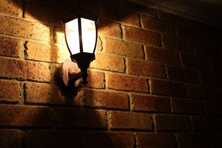 lit lamp: Lit lamp on brick wall Stock Photo