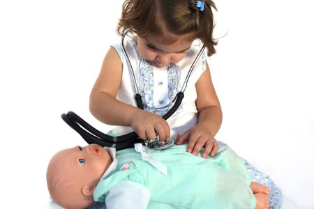 doctor toys: Cute little girl listening to her dolls chest with a medical stethoscope Stock Photo