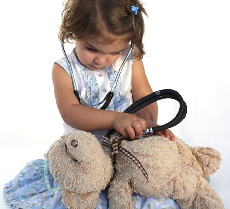 Cute little girl consulting teddy bear photo