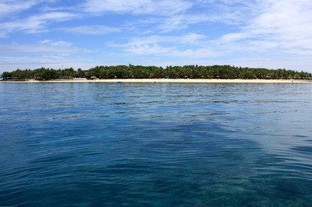Beautiful tropical island on the horizon between sky and ocean photo