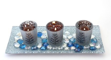 Three candles in decorative holders on a glass plate with coloured pebbles, over white.  Christmas theme. photo
