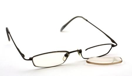 Broken glasses rim on white background, lens fallen out