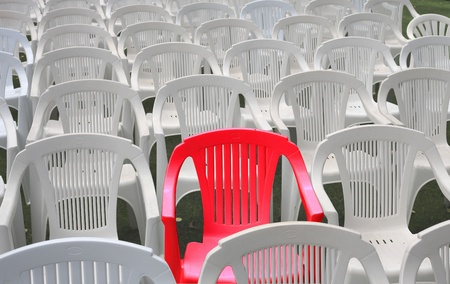 reserved seat: One red chair among many white plastic chairs   Special, or reserved seating