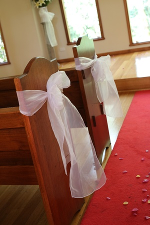 Decorations at wedding chapel -white bows on pews, red carpet with flower petals down the aisle Stock Photo