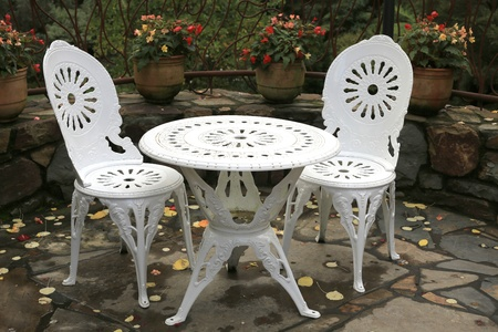 Ornate table and two chairs in outdoor entertaining area photo