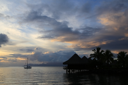 Tahiti sunset with boat and over water bungalows photo