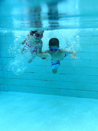 Girl and boy diving and having fun underwater