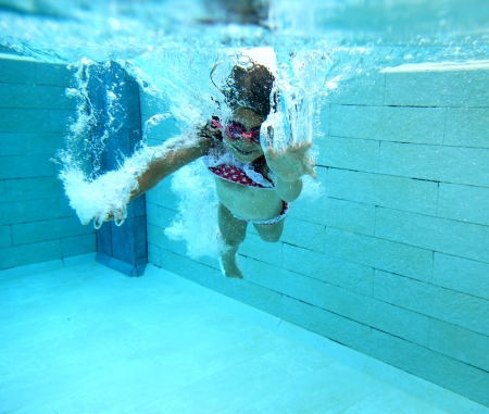 Happy little swimmer girl with bubbles in a swimming pool photo