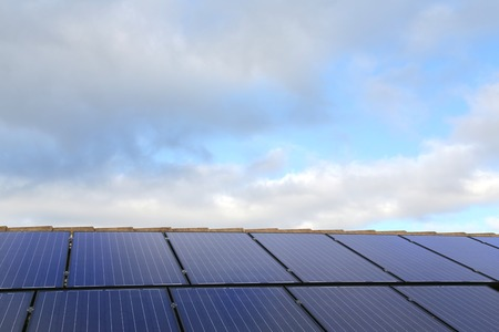 Solar panels on a house roof, with sky background