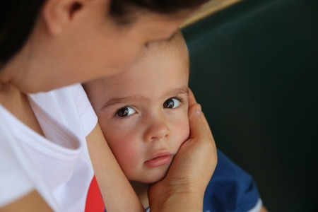 child protection: Cute little boy looking intently, with mother lovingly holding him