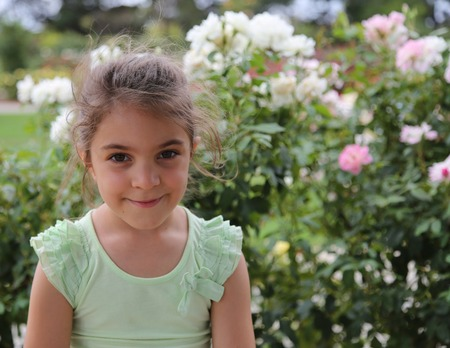 cute little girl smiling: Cute little girl smiling and looking at camera, with rose bushes in the background Stock Photo