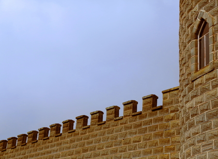 battlements: Part of a stone tower and wall with battlements from a medieval castle Stock Photo