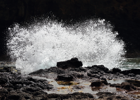 Wave crashing on rocks and splashing foam