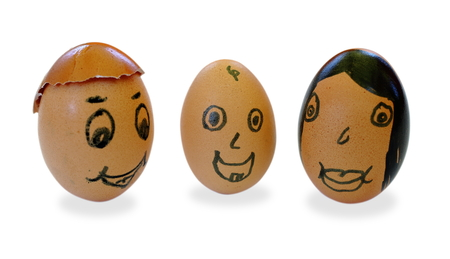 Three faces drawn on eggs, representing a family with a baby
