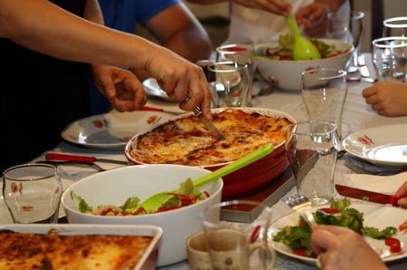 Family meal, with lady cutting the lasagna Stock Photo