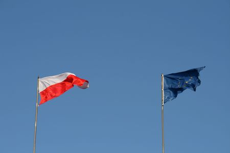 polish and european union flags on the wind