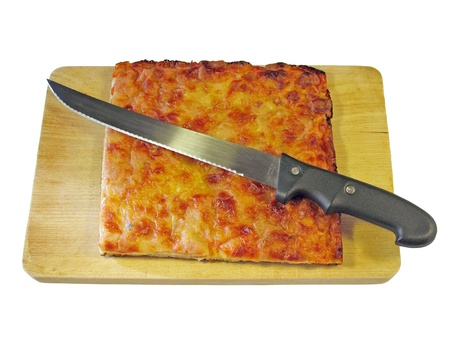 Slice of pizza on a cutting board with knife