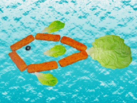 Fish formed by fish sticks, lettuce leaves and a black olive Stock Photo