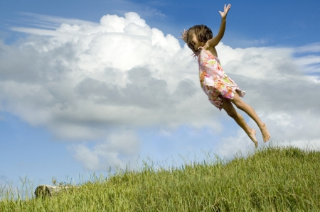 little girl jumping high in the air, grass and sky photo