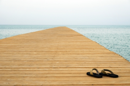 flip flops: thongs on pier with sea at background