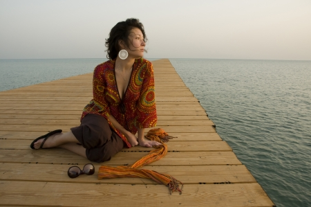 Girl sitting on pier in the morning Stock Photo