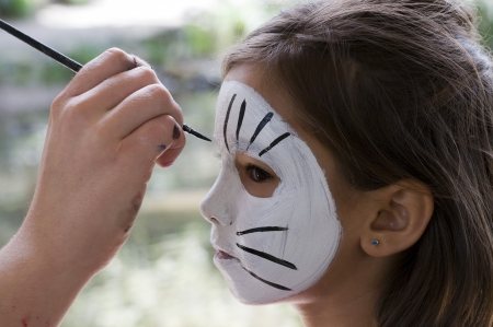 pintura en la cara: Chica obtener su cara pintada Foto de archivo