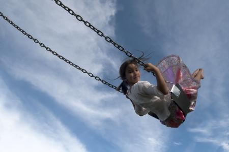 columpio: Chica balanceándose en el aire Foto de archivo