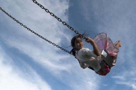 Girl swinging high in the air photo