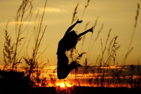 live happy: dark silhouette of the jumping girl on a background of a decline