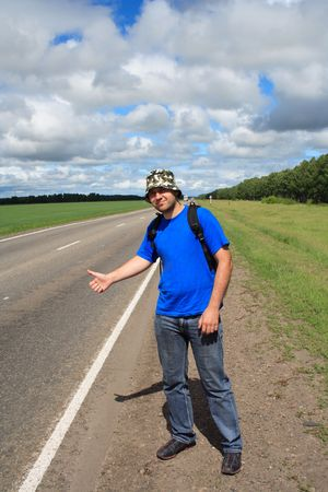 pilgrim journey: man costs on a roadside of road and stops gesture passing machines