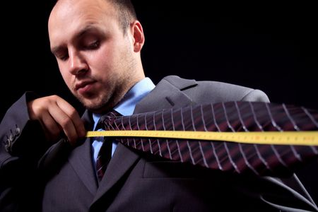 imperturbable: man, dressed in a business suit, measures the tie Stock Photo