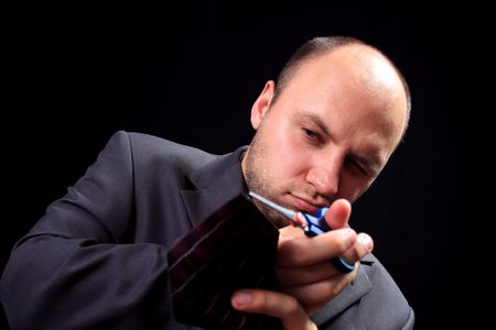 imperturbable: man in a business suit scissors the tie, on a black background