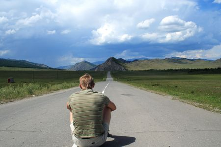 pilgrim journey: man sits in the middle of road of the leader to mountains Stock Photo