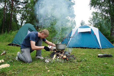 image of the guy planting a fire and tents on the nature photo