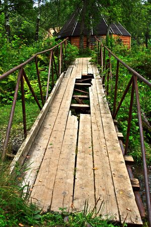 holey: old, holey bridge through a stream surrounded by a bush Stock Photo