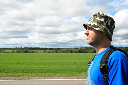 pilgrim journey: man on edge of road on a background of clouds and the blue sky