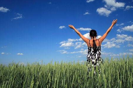 lifted hands: girl costs in a floor with the hands lifted upwards, on a background of clouds in the blue sky Stock Photo