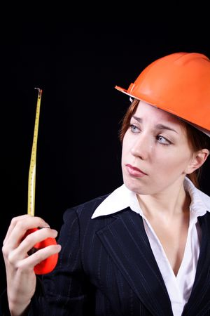 imperturbable: girl in a business suit with a roulette and in a helmet on a black background Stock Photo
