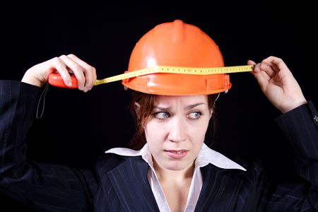 imperturbable: girl measures by a roulette the helmet on a black background