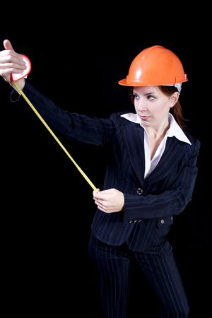 girl in a business suit with a roulette and in a helmet on a black background photo