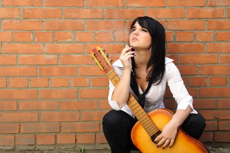 street musician: woman near a brick wall with a cigarette and a guitar