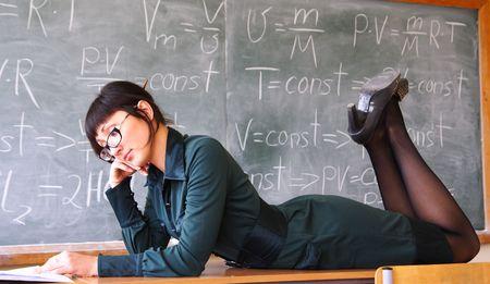 sexy school girl: beautiful student lays on a school desk near a blackboard